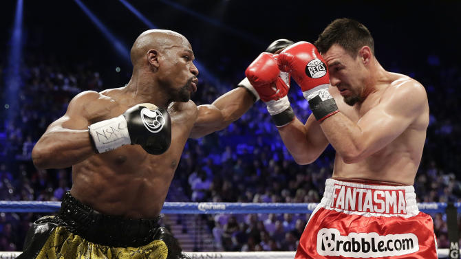 Floyd Mayweather Jr., left, throws a jab at Robert Guerrero in the third round during a WBC welterweight title fight, Saturday, May 4, 2013, in Las Vegas.  (AP Photo/Isaac Brekken)