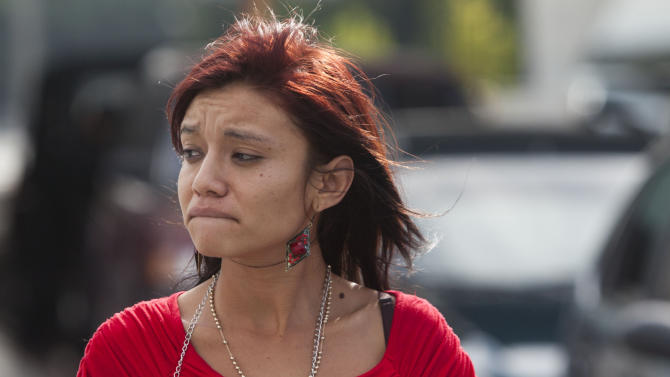 Sam, the Belizean girlfriend of software company founder John McAfee, reacts after he arrived to La Aurora international airport after being released from a detention center in Guatemala City, Wednesday, Dec. 12, 2012. McAfee, who is being deported to the U.S., was detained last week for immigration violations after he sneaked into Guatemala from neighboring Belize, where authorities sought to question him about the murder of his neighbor. (AP Photo/Moises Castillo)