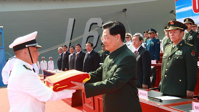 """In this photo provided by China's Xinhua News Agency, Chinese President Hu Jintao, center, endorses the flag of the People's Liberation Army (PLA) to the naval unit that receive the aircraft carrier """"Liaoning"""" at the carrier handover ceremony at a naval base in Dalian, northeast China's Liaoning Province, Tuesday, Sept. 25, 2012.  China formally entered its first aircraft carrier Liaoning  into service on Tuesday, underscoring its ambitions to be a leading Asian naval power, although the ship is not expected to carry a full complement of planes or be ready for combat for some time.  (AP Photo/Xinhua, Zha Chunming) NO SALES"""