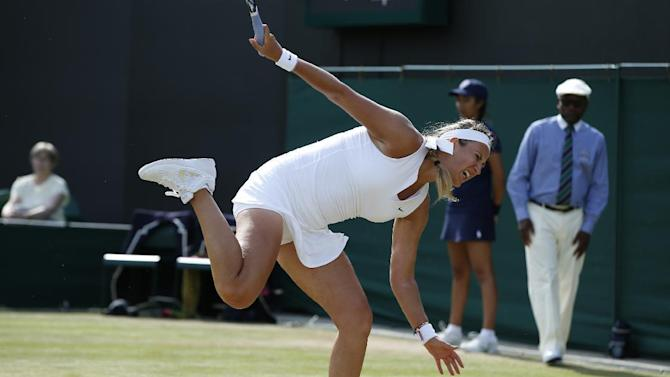 Victoria Azarenka of Belarus stumbles during her singles match to Kristina Mladenovic of France, at the All England Lawn Tennis Championships in Wimbledon, London, Friday July 3, 2015. (AP Photo/Alastair Grant)