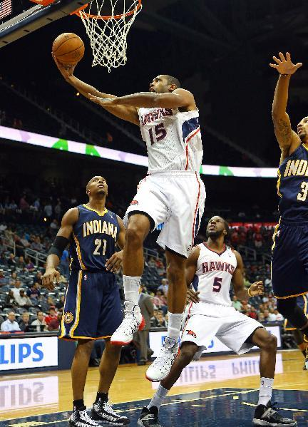Atlanta Hawks power forward Al Horford (15) shoots past Indiana Pacers power forward David West (21) during the first half of a preseason NBA basketball game on Tuesday, Oct. 22, 2013, in Atlanta