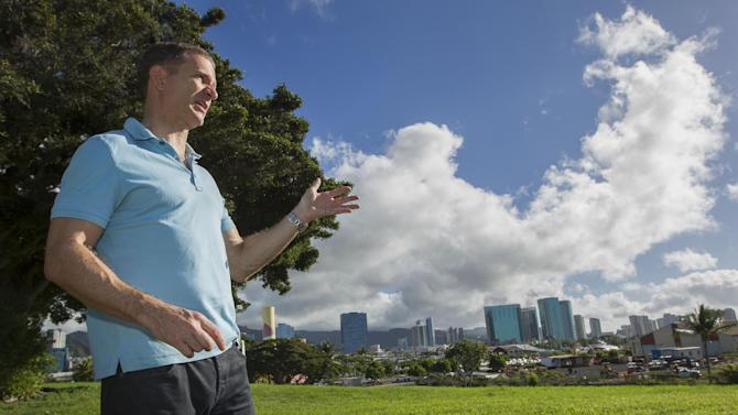In this Tuesday, Dec. 24, 2013 photo, Robert Perkinson, an associate professor at the University of Hawaii at Manoa, talks about the possible location in the Kakaako district of Honolulu to be considered for the Barack Obama Presidential Library. The plot of land can be seen to the far right. (AP Photo/Eugene Tanner)