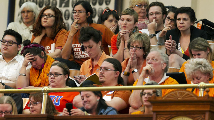 Women's rights protesters react in gallery of the House of Representative Chambers as State Rep. Jodie Laubenberg, R-Parker, works on the second reading of Senate Bill 5, the bill she sponsored, during debate on abortion held on the House floor of the State Capitol in Austin, Texas, on Sunday, June 23, 2013. If passed, the bill would ban abortions after 20 weeks, require that they take place in surgical centers, and restrict where and when women can take abortion-inducing pills_and force 37 out of 42 abortion clinics in Texas to close and undergo millions of dollars in upgrades. (AP Photo/Statesman.com, Rodolfo Gonzalez)
