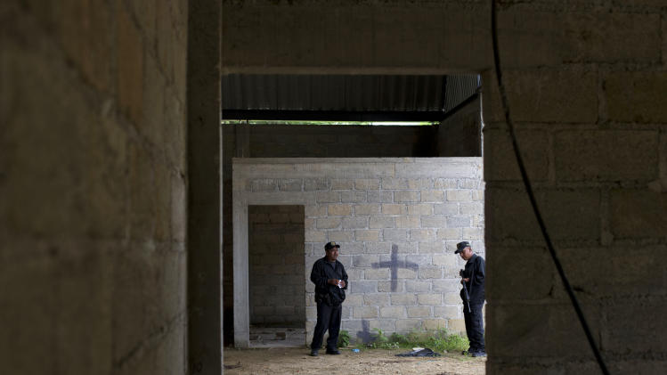 FILE - In this Thursday, July 3, 2014, file photo, state police stand inside a warehouse where a black cross covers a wall near blood stains on the ground, after a shootout between Mexican soldiers and alleged criminals on the outskirts of the village of San Pedro Limon, in Mexico state, Mexico. The New York-based group Human Rights Watch is calling on Aug. 22, 2014, on the Mexican government to fully investigate a supposed shootout in which soldiers killed 22 suspects while suffering only one soldier wounded. (AP Photo/Rebecca Blackwell, File)