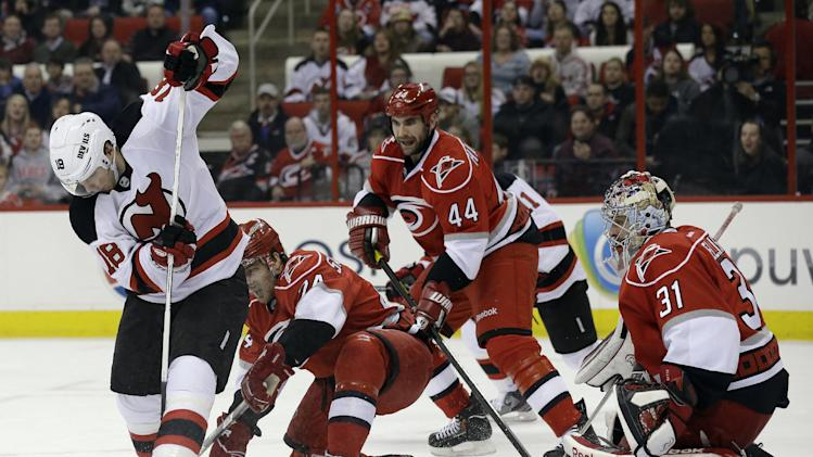 Carolina Hurricanes goalie Dan Ellis (31) and teammates Jay Harrison (44) and Bobby Sanguinetti defend against  New Jersey Devils' Steve Bernier (18) during the first period of an NHL hockey game in Raleigh, N.C., Thursday, March 21, 2013. (AP Photo/Gerry Broome)