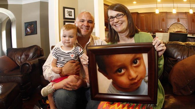 In this Monday, Aug. 6, 2012 photo, Ryan Hooker holds his 2 year-old daughter Ellyson as Jessica Hooker holds a photograph of their 6 year-old Guatemalan son Daniel, at their home in Maryville, Tenn. Daniel was 18 months old when the Tennessee couple began the process to adopt him in Guatemala. They just got him at age 6. His is one of hundreds of adoption cases that were put in limbo five years ago, when the Guatemalan government declared a moratorium on international adoptions because of irregularities and fraud. (AP Photo/Wade Payne)