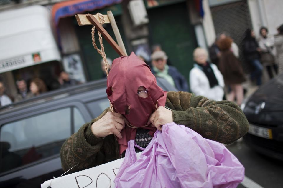 A demonstrator puts a rope around his neck while getting ready to participate in an anti-austerity protest march in Lisbon Saturday, Feb. 16 2013. The protest was called by CGTP, the Portuguese confederation of workers unions. (AP Photo/Armando Franca)