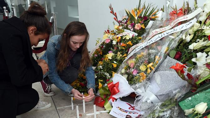 Tourists light candles at the national Bardo Museum in Tunis in memory of the victims of a jihadists attack which killed 21 people, including 20 tourists, during the official re-opening of the museum following the massacre on March 27, 2015