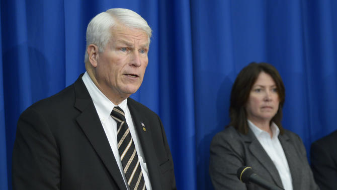 University of Central Florida president John Hitt, left, answers questions during a news conference after the apparent suicide of UCF student James Oliver Seevakumaran in his dorm room, Monday, March 18, 2013, in Orlando, Fla. Seevakumaran's body was found with an assault rifle and explosive devices.  Listening is ATF special agent Julie Torrez. (AP Photo/Phelan M. Ebenhack)