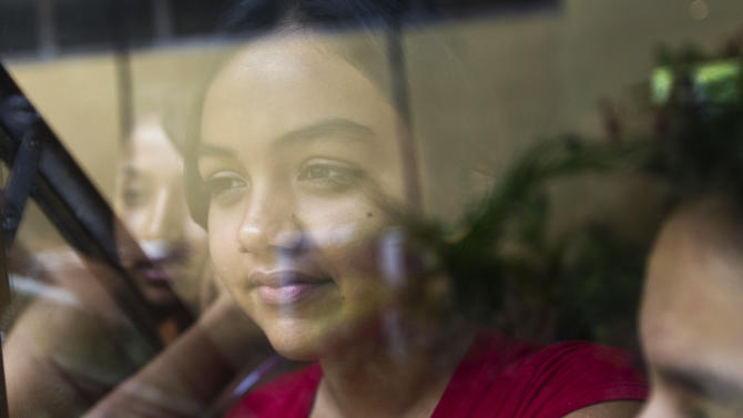 "Mayerling Rivera, a Nicaraguan girl suffering from leukemia, looks through a window during preparations of a ""quinceanera"" party in Managua, Nicaragua, Saturday Sept. 21, 2013. For each of the past five years, Nicaragua's Association of Mothers and Fathers of Children with Cancer and Leukemia has put on a ""quinceanera"" party for girls from poor, rural families, teens who have the added burden of dealing with cancer. This year's party feted 37 girls between ages 14 and 16 on Saturday night at a hotel in Nicaragua's capital.(AP Photo/Esteban Felix)"