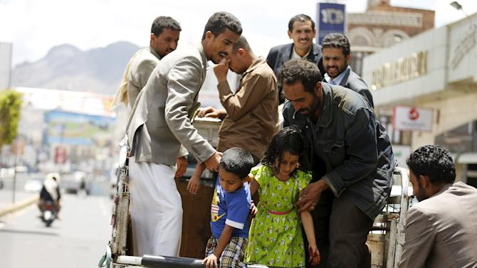 People help children step out of a truck taxi in Yemen's capital Sanaa