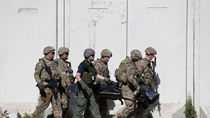 U.S. troops carry the dead body of a soldier from a NATO-led international military force, at the site of a suicide attack in Kabul