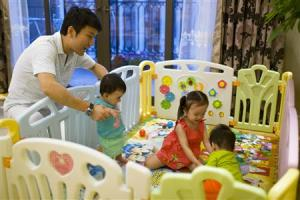 Tony Jiang poses with his three children at his house in Shanghai