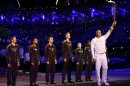Britain's Steve Redgrave holds the Olympic Flame aloft during the opening ceremony of the London 2012 Olympic Games