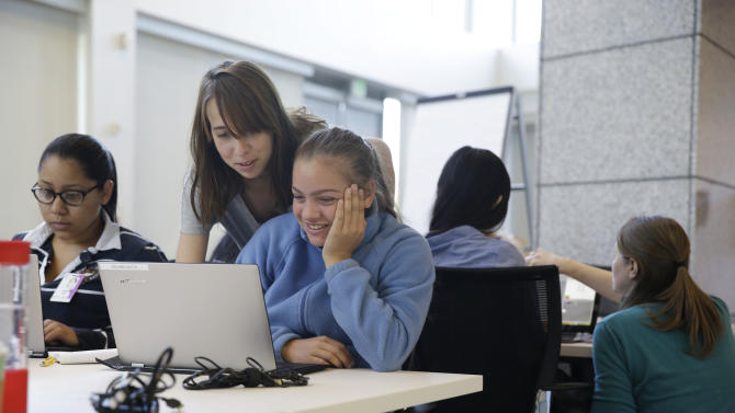 In this photo taken Wednesday, June 18, 2014, teacher assistant Margarita Sokolova, second from left, helps Giuliana Zautta, 17, of Menlo Park, Calif., during a Girls Who Code class at Adobe Systems in San Jose, Calif. Google is partnering with Girls Who Code, a national non-profit organization that aims to inspire, educate and equip young women for futures in the computing-related fields. (AP Photo/Eric Risberg)
