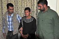Najibullah (C), who confessed to murdering Mah Gul, 20, after she refused to be a prostitute, walks handcuffed with two Afghanistan security personnel in Herat