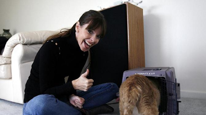 """IMAGE DISTRIBUTED FOR BANFIELD PET HOSPITAL - ANIMAL PLANET pet trainer Victoria Stilwell reacts after Danielle DeLozier's cat Pooh enters the cat carrier successfully during an in-home training session on Wednesday, Oct. 10, 2012 in Brownstown, Mich. DeLozier won Banfield Pet Hospital's Cat vs. Carrier """"inFURvention"""" contest and received an in-home training session with Stilwell and free preventive care for a year from Banfield Pet Hospital. (Photo by Gary Malerba/Invision for Banfield Pet Hospital/AP Images)"""