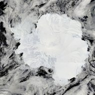 "This is Antarctica's ice-covered landscape. The surface appears rough where the Transantarctic Mountains curve in a shallow ""s"" from the shore of the Ross Sea to the Ronne Ice Shelf. The Polar Plateau in the center of the continent is smooth, s"