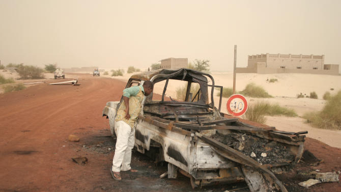 A man takes a close look at a burned-out truck in Timbuktu, Mali, Thursday Jan. 31, 2013.  Islamic militants fled from the area when French special forces parachuted in to liberate the city of Timbuktu several days ago. (AP Photo/Harouna Traore)
