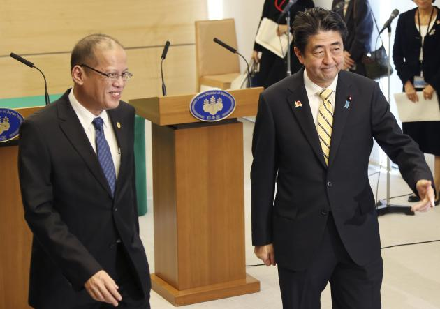 Philippines President Benigno Aquino (L) and Japanese Prime Minister Shinzo Abe leave after their joint news conference at the prime minister's official residence in Tokyo