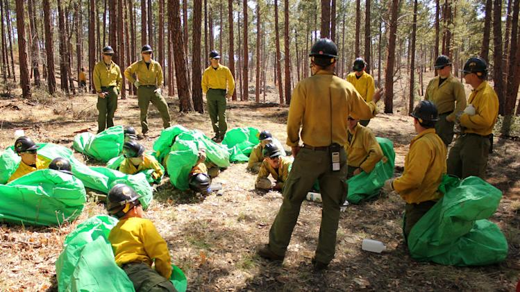 In this 2012 photo provided by the Cronkite News, Phillip Maldonado, a squad leader with the Granite Mountain Hotshots, trains crew members on setting up emergency fire shelters. On Sunday, June 30, 2013, 19 members of the Prescott, Ariz.-based crew were killed in the deadliest wildfire involving firefighters in the U.S. for at least 30 years. The firefighters were forced to deploy their emergency fire shelters - tent-like structures meant to shield firefighters from flames and heat - when they were caught near the central Arizona town of Yarnell, according to a state forestry spokesman. (AP Photo/Cronkite News, Connor Radnovich)