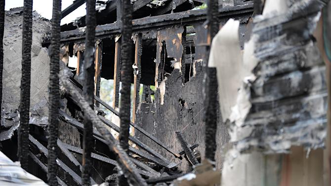 Charred beams and framing studs remain after a fatal house fire killed five, including four children, in Newnan, Ga., Saturday, April 27, 2013. The fire killed Alonna T. McCrary, 27, as well as her 5-year-old daughter Eriel McCrary and 2-year-old daughter Nikia White, according to Glenn Allen, the Georgia state Insurance commissioner's spokesman. Two other children, Messiah White, 3, and McKenzie Florence, 2, also died. Allen said the two were sleeping over at the home. A fifth child, 11-year-old Nautica McCrary, escaped the burning home and was taken to a hospital to be treated for smoke inhalation. (AP Photo/David Tulis)