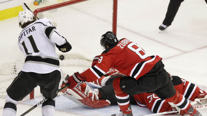 Los Angeles Kings' Anze Kopitar, left, of Slovenia, scores past New Jersey Devils' Martin Brodeur, bottom, and Dainius Zubrus, of Lithuania, during overtime in Game 1 of the NHL hockey Stanley Cup finals Wednesday, May 30, 2012  in Newark, N.J. The Kings won 2-1. (AP Photo/Kathy Willens)