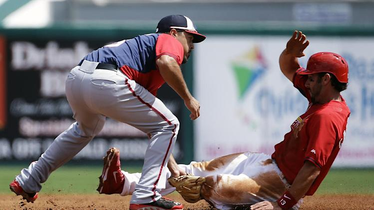 St. Louis Cardinals' Matt Carpenter, right, is tagged out while trying to steal second base by Washington Nationals' Anthony Rendon, left, during the first inning of an exhibition spring training baseball game, Saturday, March 8, 2014, in Jupiter, Fla
