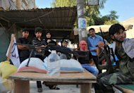 Syrian people stand next to a checkpoint manned by rebels in the northern city of Aleppo. Rebels accused strongman Bashar al-Assad on Tuesday of moving chemical weapons to Syria&#39;s borders, a day after his beleaguered regime said it would use its stockpiles if attacked
