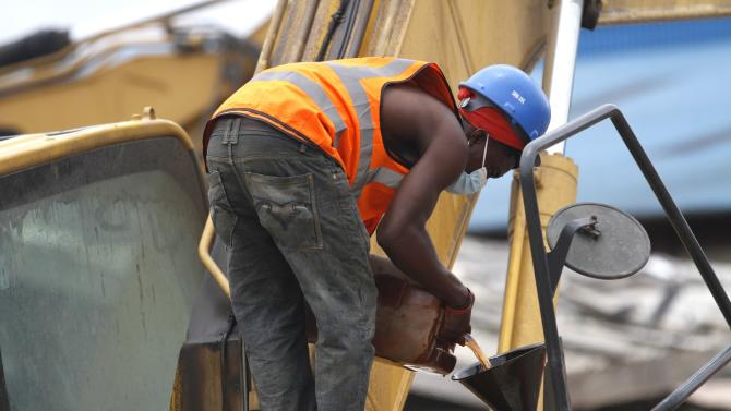 A rescue worker pours fuel into an excavator at the site of a collapsed building at the Synagogue Church of All Nations in the Ikotun-Egbe neighbourhood of Nigeria's commercial capital Lagos