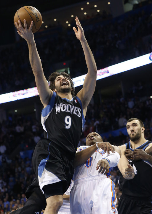 Minnesota Timberwolves guard Ricky Rubio (9) shoots in front of Oklahoma City Thunder guard Russell Westbrook (0) and Timberwolves' Nikola Pekovic, right, in the first quarter of an NBA basketball gam