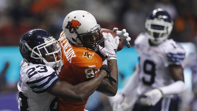 BC Lions' Emmanuel Arceneaux is tackled by Toronto Argonauts' Vincent Agnew during the second half of their CFL football game in Vancouver