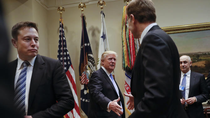 President Donald Trump greets Wendell P. Weeks, right, Chief Executive Officer of Corning, as he host breakfast with business leaders in the Roosevelt Room of the White House in Washington, Monday, Jan. 23, 2017. On the left of is Elon Musk, CEO of SpaceX and Tesla Motors. (AP Photo/Pablo Martinez Monsivais)
