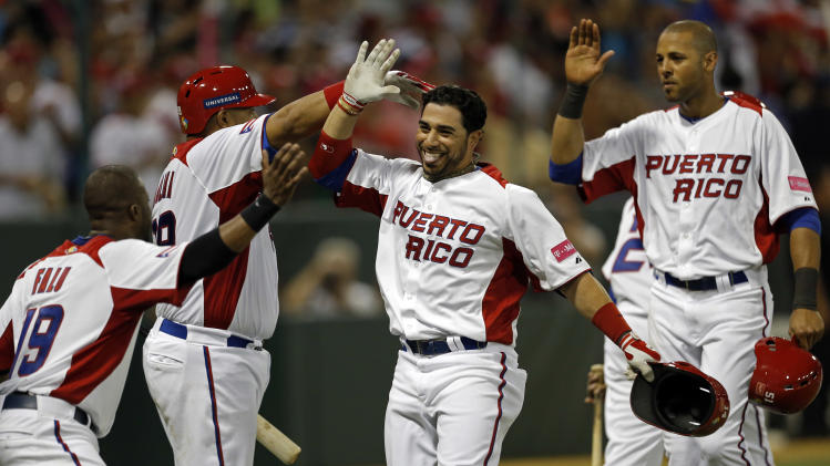 Puerto Rico's Mike Aviles, third from left, highs five with teammates after hitting a two run home run in the 4th inning of the World Baseball Classic first round game against the Dominican Republic in San Juan, Puerto Rico, Sunday, March 10, 2013. (AP Photo/Andres Leighton)
