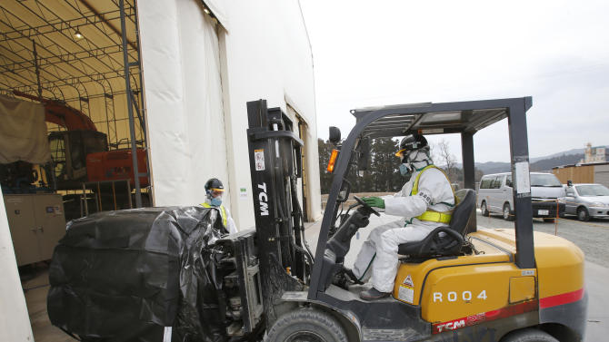 In this Friday, March 1, 2013 photo, radioactive waste packed in a protective storage bag is transported from a workplace to be placed at an adjacent temporary waste storage site in Naraha, Fukushima prefecture near the tsunami-ravaged Fukushima Dai-ichi nuclear power plant in Japan. Two years after the triple calamities of earthquake, tsunami and nuclear disaster ravaged Japan's northeastern Pacific coast, radioactive and chemical contamination remains a threat as clean-up projects face troubles with organized crime and mishandling.    (AP Photo/Shizuo Kambayashi)