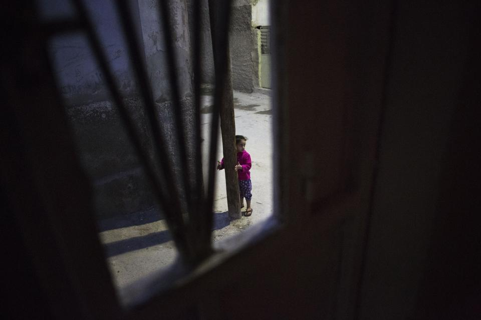 In this Monday, Oct. 21, 2013 photo, a Syrian refugee girl is seen through the window of her family home as she plays on the street the outskirts of Zarqa, Jordan's industrial center where thousands of Syrian refugees are living, northeast of the capital Amman. More than 420,000 Syrian refugees have settled in Jordan's cities, struggling for survival on U.N. foods stamps and straining the meager resources of a country that absorbed millions of exiles from the region's hotspots in the past.(AP Photo/Manu Brabo)