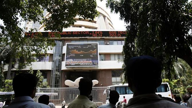 People look at a large screen displaying India's benchmark share index on the facade of the Bombay Stock Exchange building in Mumbai