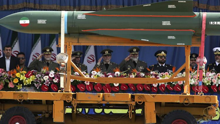 "An Asre-67 missile is displayed by the Iranian army as President Mahmoud Ahmadinejad, left, reviews a military parade marking National Army Day, along with military commanders, in front of the mausoleum of the late revolutionary founder Ayatollah Khomeini, just outside Tehran, Iran, Thursday, April 18, 2013. Ahmadinejad slammed ""foreign presence"" in the Persian Gulf, claiming it's the source of insecurity in the region. (AP Photo/Vahid Salemi)"
