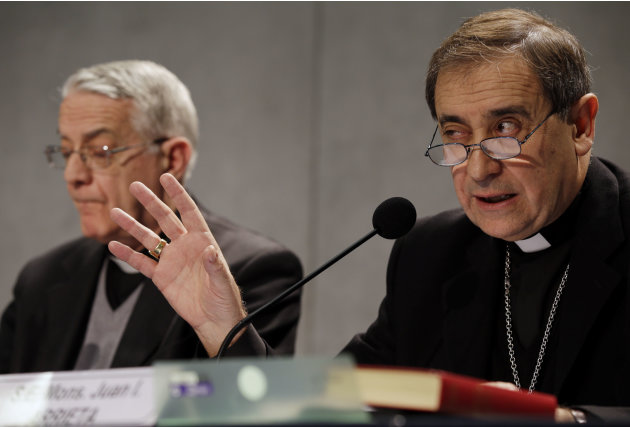 Bishop Juan Ignacio Arrieta, right, flanked by Vatican spokesman, Rev. Federico Lombardi gestures during a press conference at the Vatican, Friday, Feb. 22, 2013. Pope Benedict XVI may enact a new law