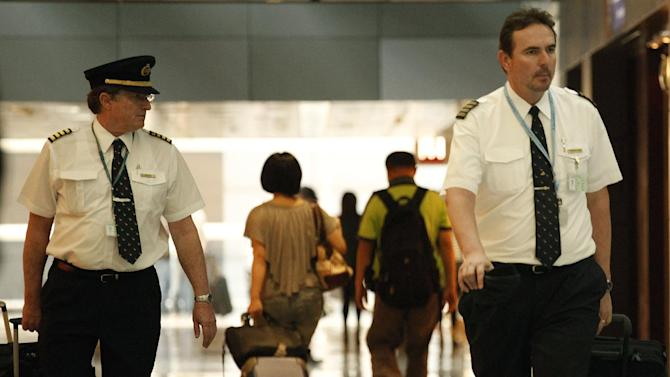 In this Nov. 30, 2011 photo, two pilots from Cathay Pacific walk in the Hong Kong International Airport in Hong Kong. The U.S. airline industry will need to hire 1,900 to 4,500 new pilots annually over the next 10 years due to an expected surge in retirements of pilots reaching age 65 and increased demand for air travel, the Government Accountability Office said in the report obtained late Thursday, Feb. 27, 2014. (AP Photo/Vincent Yu, File)