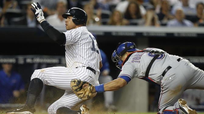 New York Yankees' Alex Rodriguez slides past Texas Rangers catcher Yorvit Torrealba to score during the fifth inning of a baseball game Wednesday, June 15, 2011, at Yankee Stadium in New York. (AP Photo/Frank Franklin II)