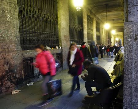 Pedestrians walk past a homeless man in Buenos Aires'financial district
