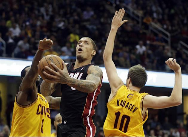 Miami Heat's Michael Beasley shoots between Cleveland Cavaliers' Earl Clark and Sergey Karasev (10) in the fourth quarter of an NBA basketball game Wednesday, Nov. 27, 2013, in Cleveland. The Heat won