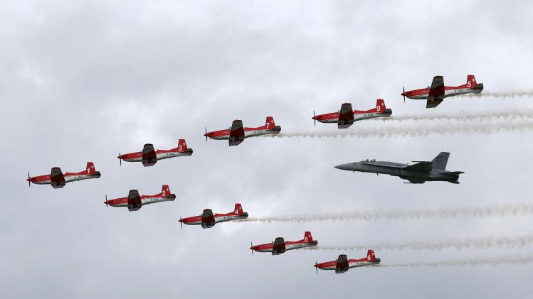 Swiss Air Force PC-7 Team performs with a F/A 18 Hornet aircraft during the Air14 airshow at the airport in Payerne
