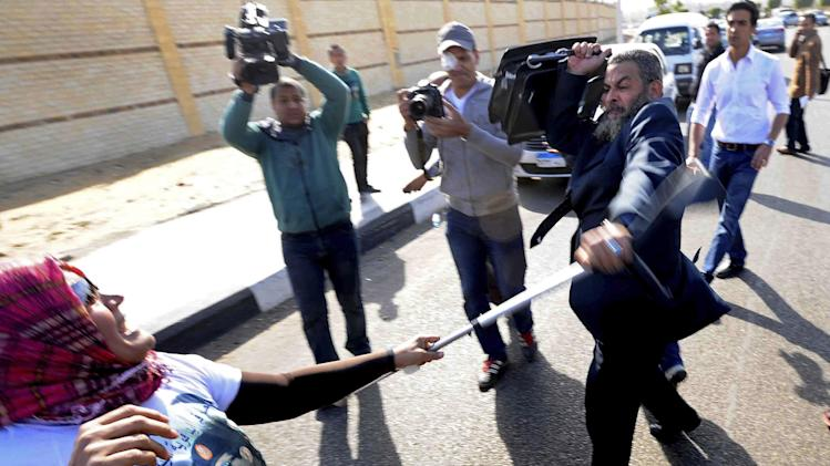 A supporter of the head of Egypt's military, Abdel-Fattah el-Sissi, left, wearing a t-shirt with his image, scuffles with a Muslim Brotherhood lawyer, Ahmed Kamel, after she struck him outside a makeshift courtroom at the national police academy, in an eastern suburb of Cairo, Egypt, Saturday, Feb. 1, 2014. The trial of Egypt's ousted president, Mohammed Morsi and 14 others also accused of inciting the killing of protesters resumed on Saturday. The trial is one of four Morsi and top leaders of his Muslim Brotherhood face with the charges levelled against them mostly carrying the death penalty. (AP Photo/Ahmed Omar)