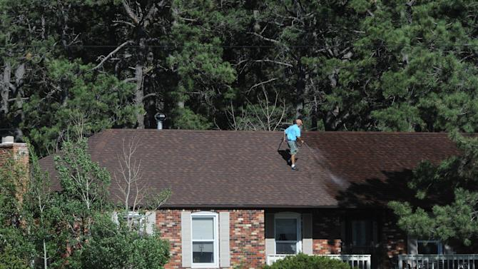 A resident sprays water on the roof of his home along Black Forest Road Tuesday afternoon, June 11, 2013, near Colorado Springs, Colo Minutes later the fire jumped the road to the south of his house. The Black Forest Fire was one of at least three significant wildfires burning in Colorado amid gusty winds and record-breaking hot, dry weather. (AP Photo/The Colorado Springs Gazette, Christian Murdock) MAGS OUT
