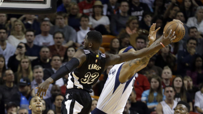 Dallas Mavericks forward Charlie Villanueva (3) tips the ball out of the hand of Miami Heat forward James Ennis (32) as he goes to the basket in the second half of an NBA basketball  game in Miami, Friday, Jan. 30, 2015. The Mavericks won 93-72. (AP Photo/Alan Diaz)