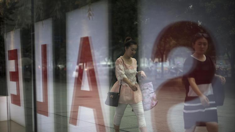 Women walk past a fashion outlet offering its summer sale at a shopping mall in Beijing, China Wednesday, July 16, 2014. China's economic growth edged up in the latest quarter and more than 7 million new jobs were created in the first half of the year, easing pressure on communist leaders as they try to prevent a precipitous slowdown in the world's second-largest economy. (AP Photo/Andy Wong)