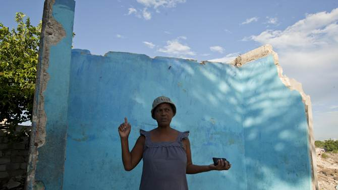 Solange Calixte 56, speaks outside her home that was damaged by heavy rain brought by Hurricane Sandy in Port-au-Prince, Haiti, Monday, Nov. 12, 2012. The rain has tapered off and floodwaters no longer claw at houses, but the situation across much of Haiti remain grim, following an autumn of punishing rains that have killed scores of people and that threaten to cause even more hunger across the nation. (AP Photo/Dieu Nalio Chery)