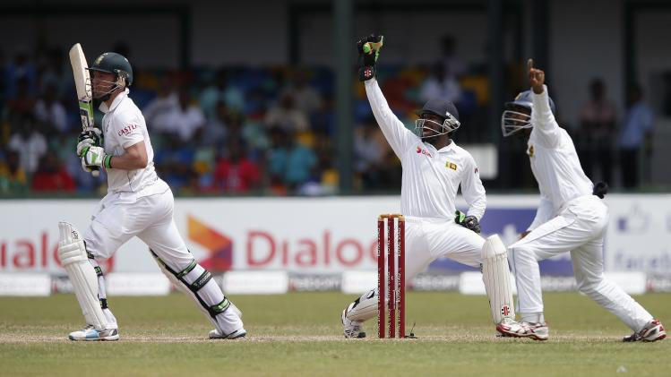 Sri Lanka's wicketkeeper Dickwella and teammate Silva appeal for a successful LBW wicket for South Africa's de Villiers during the third day of their second test cricket match in Colombo